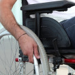 Closeup of a man's hand on the wheel of his wheelchair - Foto Stock