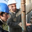 Builder's apprentice being shown how to operate machinery - Stock Photo