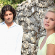 Stock Photo: Couple against stone wall