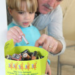 Grandfather and grandson battery sorting — Stock Photo #11747412