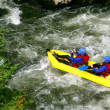 Stock Photo: Two kayaking down river rapids