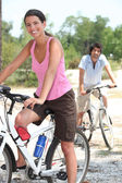Young couple riding bikes in the countryside — Stock Photo