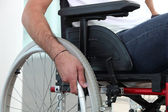 Closeup of a man's hand on the wheel of his wheelchair — Foto Stock