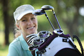 Woman with a bag full of golf clubs — Stock Photo