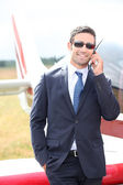 Wealthy businessman in front of an airplane — Stock Photo