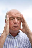 Senior man suffering from head ache — Stock Photo