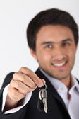 Confident estate-agent handing keys over — Stock Photo