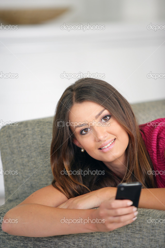 Young woman lying on the couch and sending messages with her cell  Stock Photo #11748587