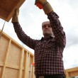 Builder putting up a wooden house — Stock Photo