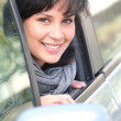 Young woman leaning out of the window of a car — Stock Photo #11750569