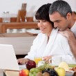 Couple eating breakfast together whilst browsing the internet — Stock Photo