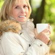Stock Photo: Mature womhaving coffee outdoors