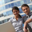 Professional couple using a laptop outside an office building — Stock Photo #11751112