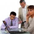 Young businesswoman with laptop and male colleagues in background — Stock Photo