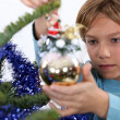 Child decorating Christmas tree - Stock Photo