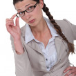 Curious businesswoman adjusting glasses — Stock Photo