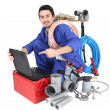 Plumber kneeling showing computer — Stock Photo #11755866