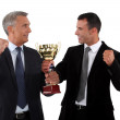 Successful businessmen holding a gold cup — Stock Photo