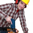Young carpenter all smiles using drill - Stock Photo