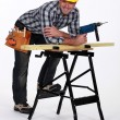 Carpenter with drill casually leaning on work bench — Stock Photo #11756707