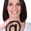 A woman showing an @ — Stock Photo