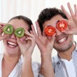 Stock Photo: Funny couple covering their eyes with fruit