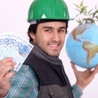 Stock Photo: Manual worker holding globe and cash