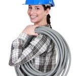 Tradeswoman carrying corrugated tubing — Stock Photo