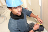 Electrician with yellow tape — Stock Photo