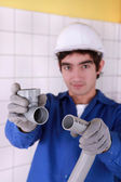 Young apprentice inserting one tube into another — Stock Photo