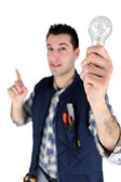 Man holding a light bulb — Stock Photo