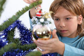 Child decorating Christmas tree — Stock Photo