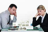 Two uninspired architects sat by model housing — Stock Photo