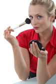 Woman applying blusher — Stock fotografie