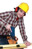 Young carpenter all smiles using drill — Stock Photo