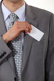 A cropped picture of a businessman putting his card in his pocket. — Stock Photo