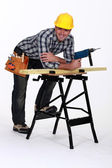 Carpenter with drill casually leaning on work bench — Stock Photo