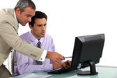 Man pointing out an error to his colleague — Stock Photo