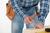 Man hammering nail into wood — Stock Photo
