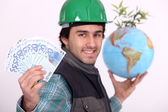 Manual worker holding globe and cash — Stock Photo