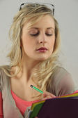 Blonde woman with downcast eyes writing — Stock Photo