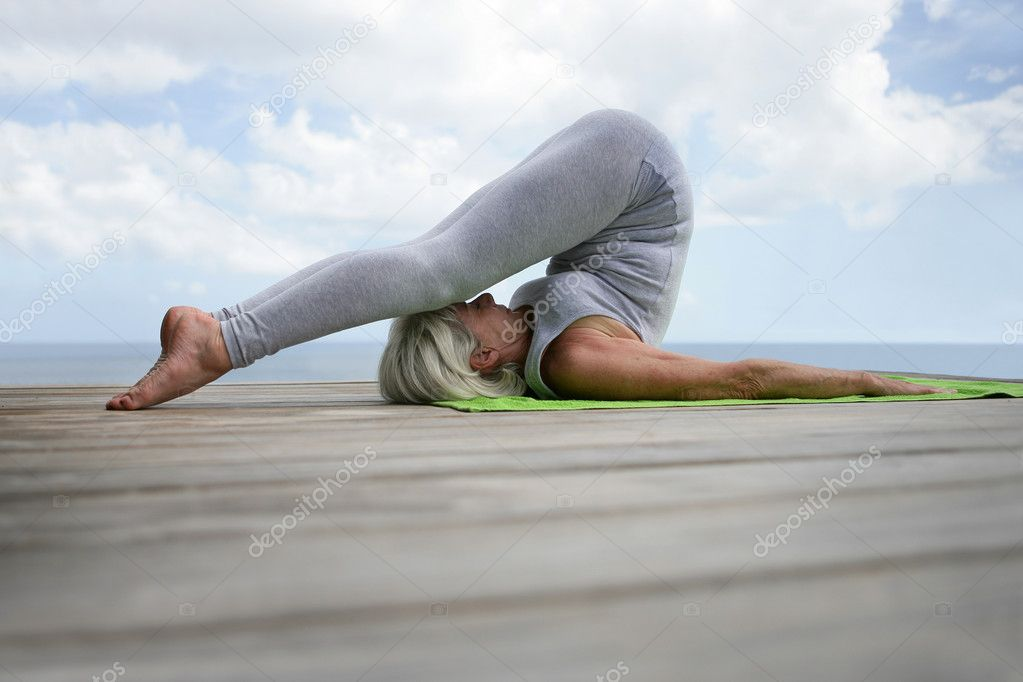 Senior woman doing yoga in a jetty  Stock Photo #11750396