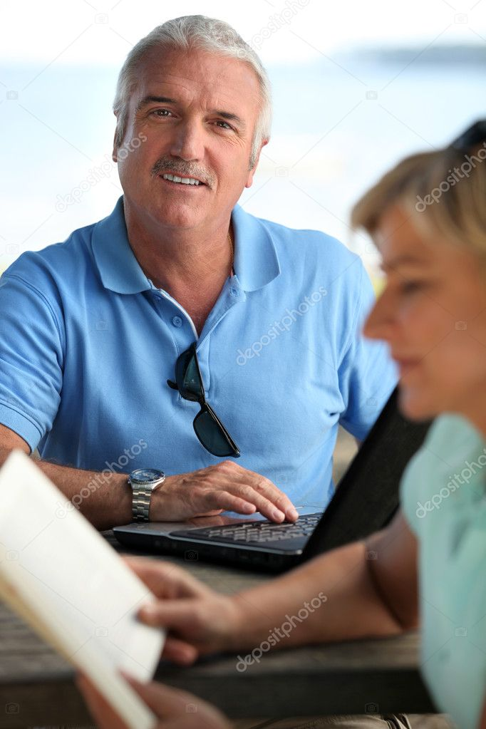 Smiling mature man using a laptop computer  Stock Photo #11751071