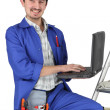Stock Photo: Plumber with computer on stepladder
