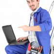Stock Photo: Msitting on ladder with laptop and plumbing tools