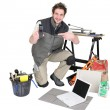 Tiler kneeling by his equipment - Stock Photo