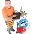 Workman posing with his laptop, tools and building materials — Stock Photo #11799074