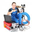 Stock Photo: Female plumber with tools of the trade, laptop computer and smartphone