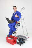 Male electrician with laptop and equipment — Stock Photo