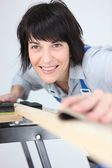 Woman sanding a plank of wood — Stock Photo